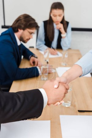 cropped shot of business people shaking hands during meeting at modern office
