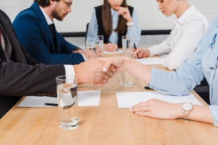 cropped shot of business partners shaking hands during meeting at modern office