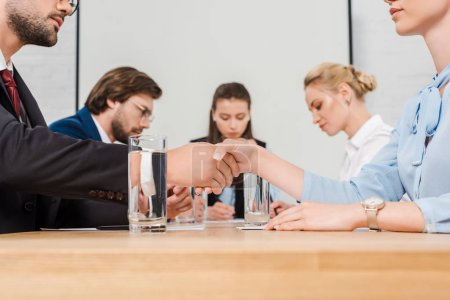 cropped shot of business partners shaking hands during conference at modern office