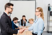 business partners shaking hands during conference at modern office