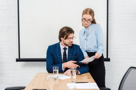 Photo for Young manageress showing documents to her boss at conference hall - Royalty Free Image