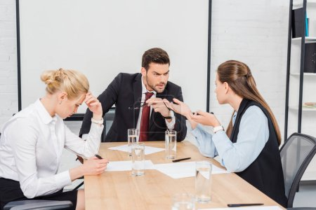 angry boss talking with his female colleagues at modern office