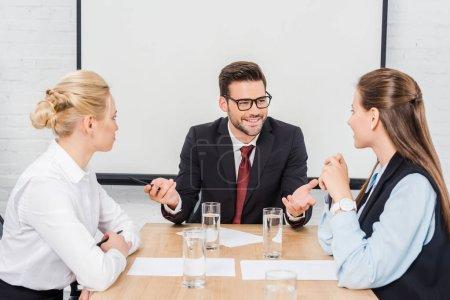 Photo pour Beau patron heureux de parler à ses collègues féminines de bureau moderne - image libre de droit