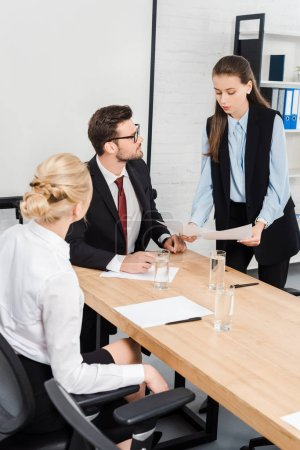 attractive young businesswomen showing documents to their boss at modern office