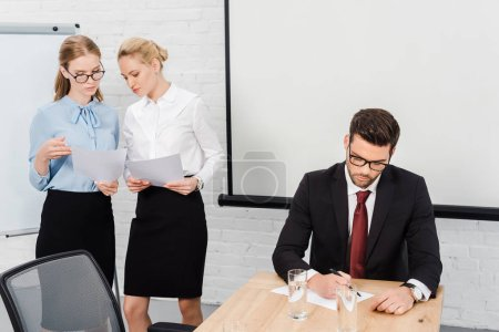 young businesswomen discussing papers while boss writing document at modern office