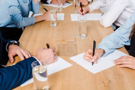Photo for Cropped shot of team of business people writing on blank papers at conference hall - Royalty Free Image