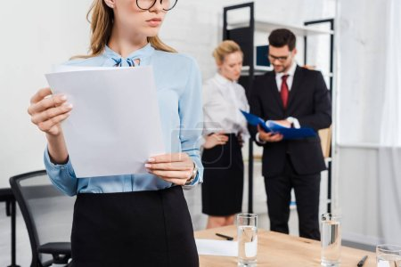 cropped shot of young businesswoman with documents standing at modern office with colleagues on background