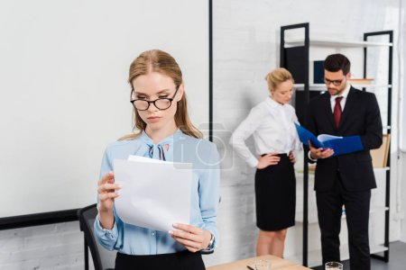 attractive young businesswoman with documents standing at modern office with colleagues on background