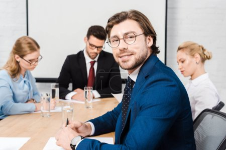 handsome young businessman sitting at conference hall with colleagues during conversation