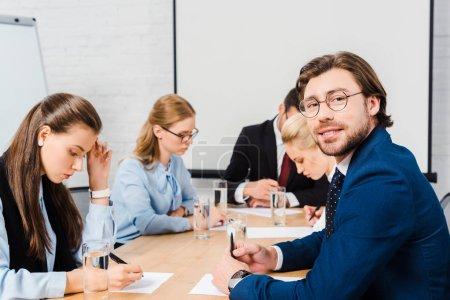 sourire de jeune homme assis à la salle de conférence avec des collègues au cours de la conversation