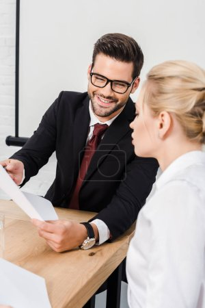 happy business partners discussing papers at modern office