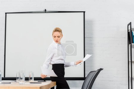 confident young businesswoman reading documents at conference hall