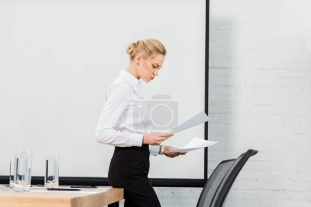 side view of young businesswoman reading documents at conference hall