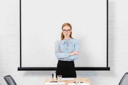 Photo pour Confiant jeune femme d'affaires avec des lunettes à la salle de conférence, regardant la caméra - image libre de droit