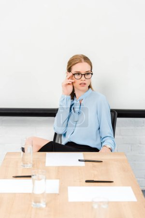 Photo for Beautiful young businesswoman sitting alone at conference hall and looking away - Royalty Free Image