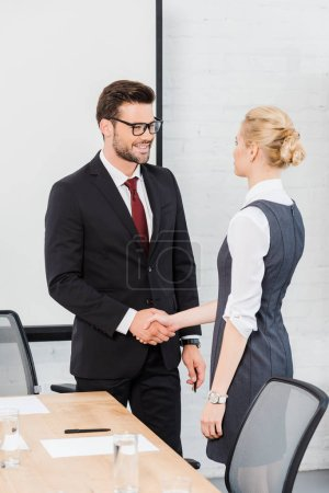 confident business partners shaking hands at modern office