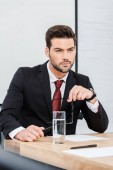 thoughtful young businessman sitting at modern office and looking away