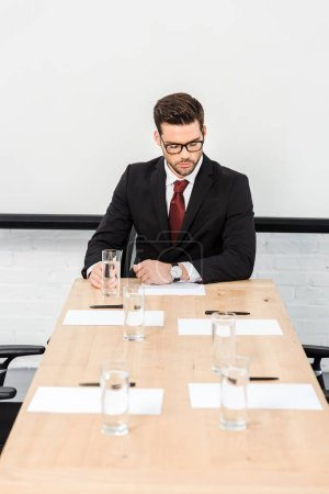 Photo for Confident young businessman working alone at conference hall - Royalty Free Image
