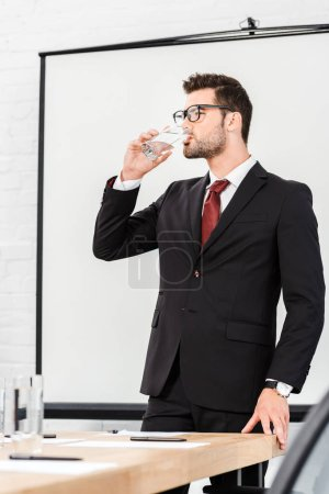 Photo for Attractive young businessman drinking water at modern office - Royalty Free Image