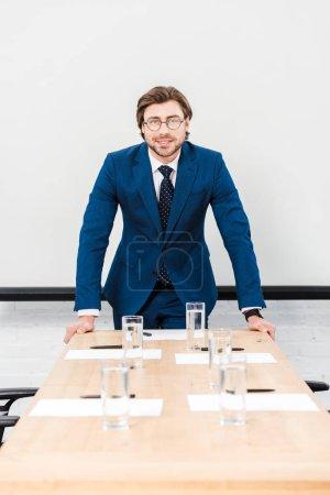 Photo pour Souriant le jeune homme d'affaires, regardant la caméra tout en se penchant sur la table à la salle de conférence et en regardant la caméra - image libre de droit