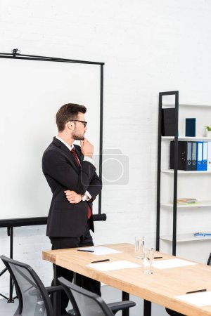 thoughtful young businessman standing at office and looking away