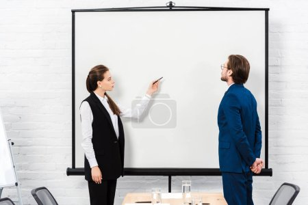 businesswoman making presentation and pointing at blank whiteboard at modern office