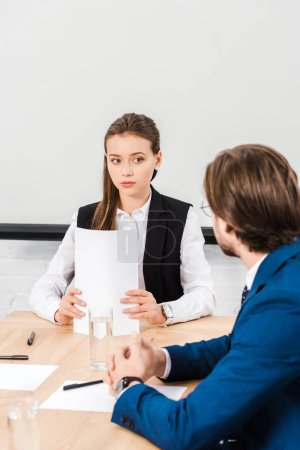 attractive young businesswoman listening to colleague while holding documents at modern office