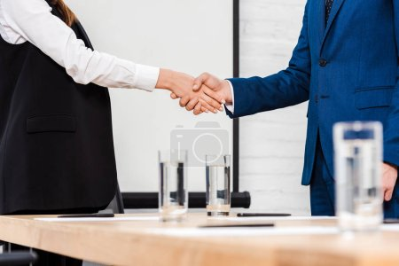 cropped shot of business colleagues shaking hands at modern office