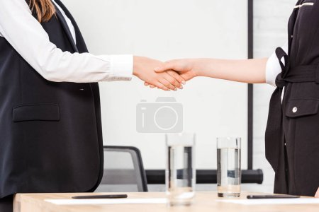 cropped shot of businesswomen shaking hands at modern office