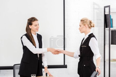 attractive young businesswomen shaking hands at conference hall