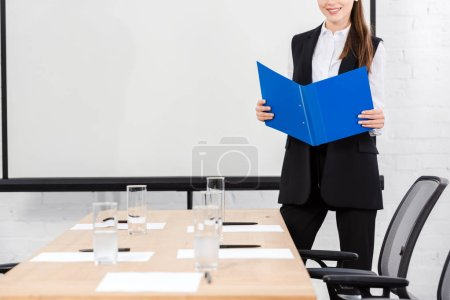 cropped shot of young businesswoman with folder standing in conference hall at modern office