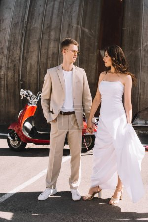 beautiful wedding couple holding hands against scooter in city