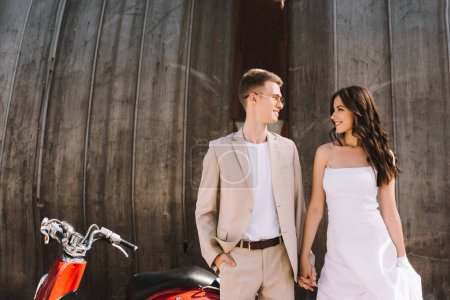 beautiful wedding couple holding hands and looking at each other against scooter in city