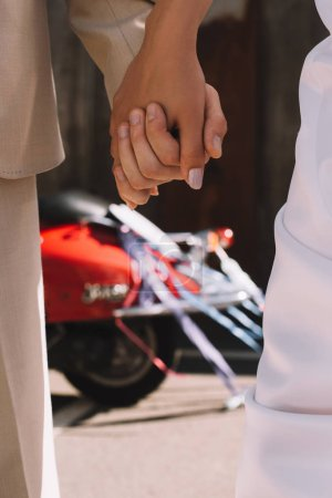 partial view of couple holding hands against red scooter