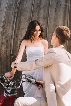 beautiful wedding couple with retro scooter in city