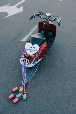 "back view of vintage moped with colorful cans, ribbons and ""just married"" heart symbol"