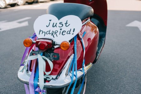 """back view of scooter with ribbons and romantic """"just married"""" heart sign"""