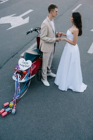 "wedding couple holding hands on road near scooter with ""just married"" heart sign and colorful cans on ribbons"