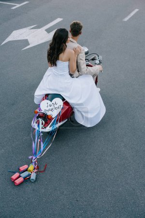 """back view of wedding couple riding scooter with """"just married"""" heart sign and colorful cans on ribbons"""