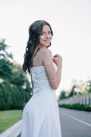 beautiful bride in white wedding dress posing outdoors