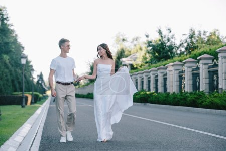attractive bride and handsome groom holding hands and walking on road