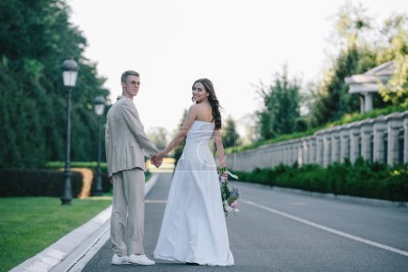 rear view of bride and groom holding hands, walking on road and looking at camera