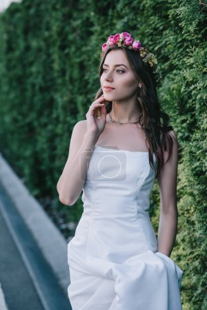 elegant bride posing in traditional white wedding dress and flower wreath