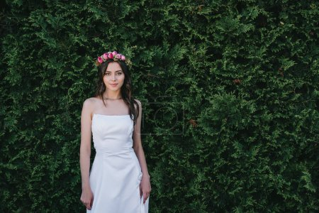 attractive bride posing in traditional white wedding dress and flower wreath
