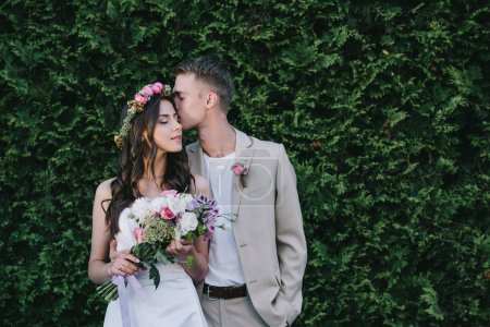 groom kissing and embracing attractive bride in wedding dress with wreath and bouquet