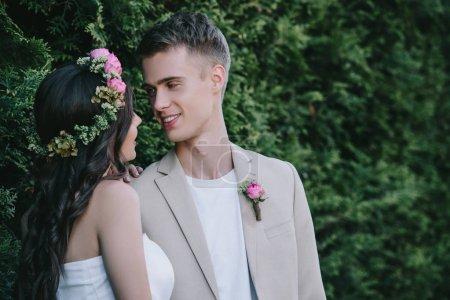 beautiful bride in floral wreath looking at happy groom