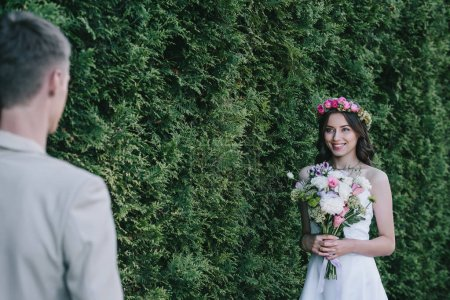 selective focus of happy attractive bride in wreath holding wedding bouquet and looking at groom