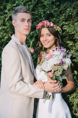 elegant wedding couple with flower bouquet looking at camera