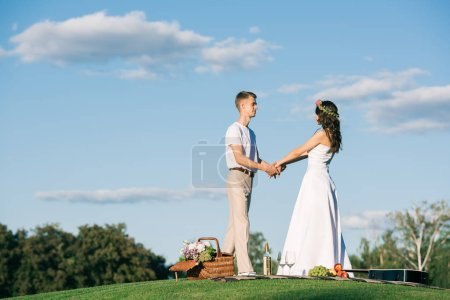 beautiful wedding couple holding hands on lawn with romantic picnic