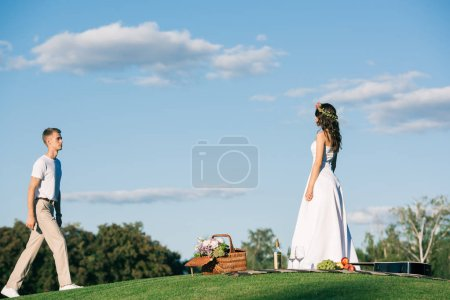 groom going to bride in white wedding dress on picnic